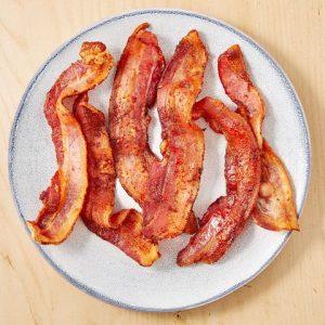 few crispy bacon slices on white plate